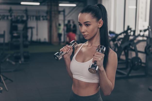 Piękna sprawności fizycznej kobieta patrzeje skoncentrowany, ćwiczy z dumbbells, kopii przestrzeń Premium Zdjęcia