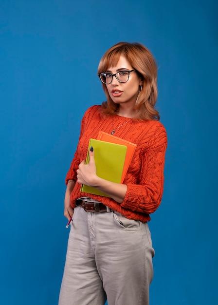 Piękna Studencka Kobieta Z Książkami. Pojedynczo Na Niebiesko. Premium Zdjęcia