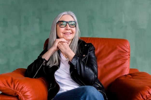 Piękna Stylowa Starsza Kobieta Z Długimi Prostymi Siwymi Włosami, Nosząca Okulary I Czarną Skórzaną Kurtkę, Siedząca W Wygodnym Miękkim Czerwonym Fotelu Na Zielonym Tle Premium Zdjęcia