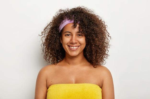 Piękna Szczęśliwa Afro Stoi Owinięta żółtym Ręcznikiem, Przygotowana Do Sauny, Ma Krzaczaste, Chrupiące Włosy, Nosi Opaskę, Czuje Się Zadowolona, że Zawsze Wygląda Młodo. Koncepcja Kobiecości, Etniczności I Dobrego Samopoczucia Darmowe Zdjęcia