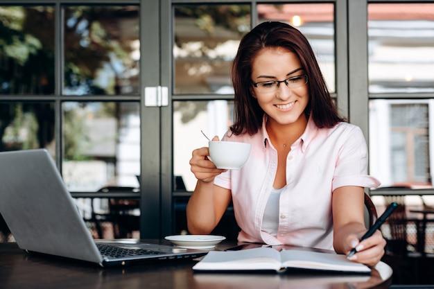 Piękna, Szczęśliwa Brunetka Trzyma Kubek W Dłoni, Pracuje Na Laptopie W Kawiarni. Premium Zdjęcia
