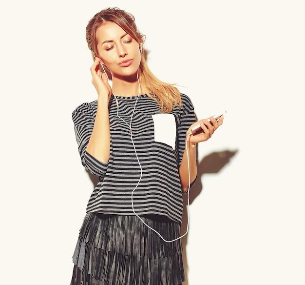 Piękna Szczęśliwa Kobieta W Przypadkowych Hipster Letnie Ubrania Na Białym Tle Słuchania Muzyki W Smartfonie Ze Słuchawkami Darmowe Zdjęcia