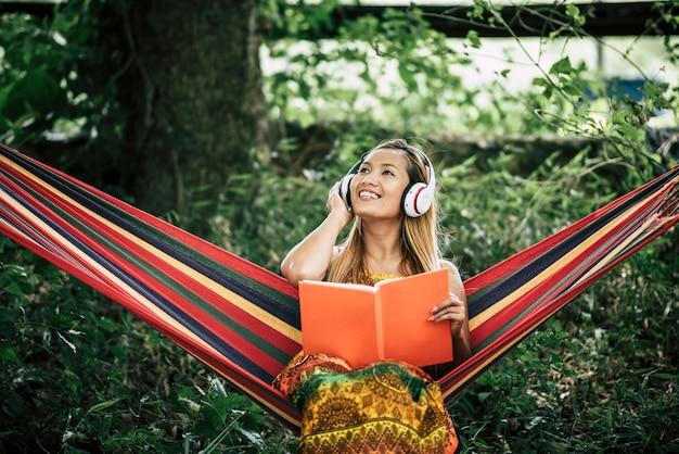 Piękna Szczęśliwa Młoda Kobieta Słucha Muzyka I Czytający Książkę Z Hełmofonami Darmowe Zdjęcia