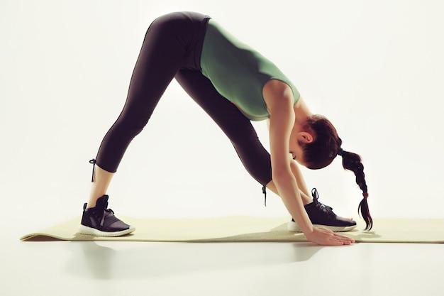 Piękna Szczupła Brunetka Robi ćwiczenia Rozciągające Na Siłowni Darmowe Zdjęcia