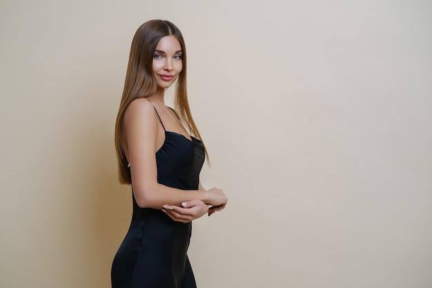 Piękna Szczupła Kobieta Stoi Z Profilu, Nosi Elegancką Czarną Sukienkę, Ma Długie Proste Włosy Premium Zdjęcia