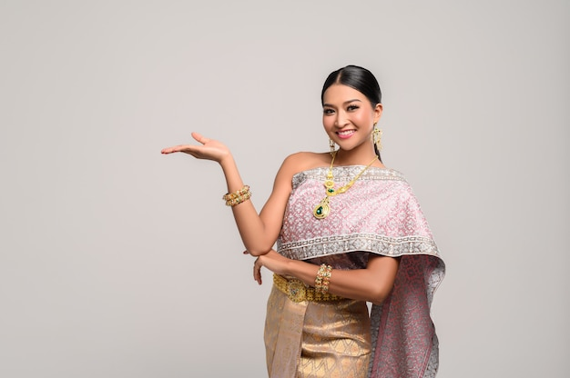 Piękna tajka nosi tajskie ubrania i otwiera dłoń w prawo Darmowe Zdjęcia