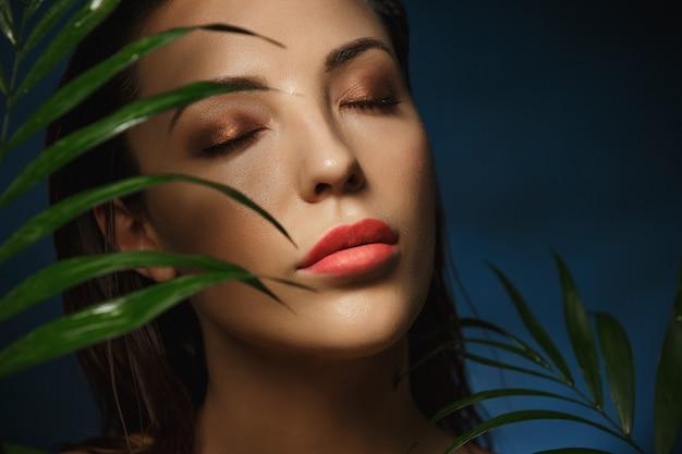 Piękna Twarz Kobiety Pod Egzotycznych Zielonych Liści. Fotografia Mody. Darmowe Zdjęcia