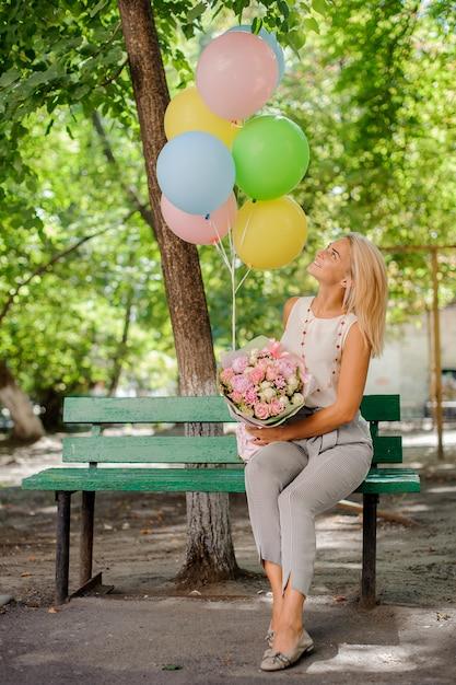 Piękna urodzinowa dziewczyna z ładnymi kwiatami i balonami Premium Zdjęcia