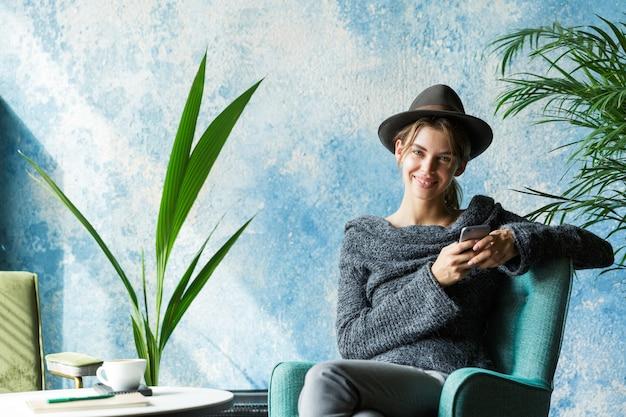 Piękna Uśmiechnięta Młoda Kobieta Ubrana W Sweter I Kapelusz Siedzi Na Krześle Przy Stoliku Kawiarnianym, Trzymając Telefon Komórkowy, Stylowe Wnętrze Premium Zdjęcia