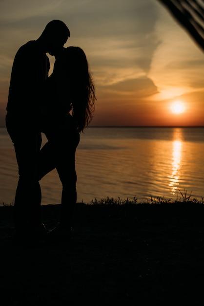 Piękna Zakochana Para, Turyści O Pełnej Wysokości świtu Patrzą Sobie W Oczy I Uśmiechają Się Premium Zdjęcia
