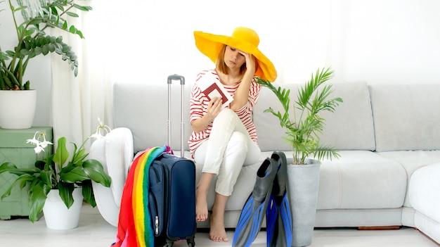 Piękna Zdenerwowana Dziewczyna W żółtym Kapeluszu Zostaje W Domu I Planuje Wyjazd Na Wakacje. Czekam Na Podróż. Premium Zdjęcia