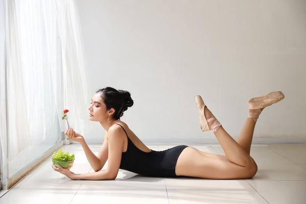 Piękna zdrowa azjatykcia młodej kobiety łasowania sałatka po stażowego baleta podczas gdy łgarski puszek Premium Zdjęcia