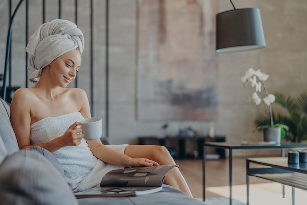Piękna Zrelaksowana Kobieta Zawinięta W Ręcznik Picia Herbaty Premium Zdjęcia