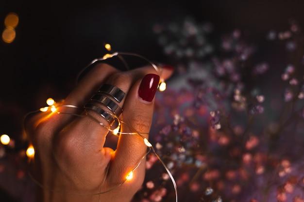 Piękne Ciemne Zdjęcie Kobiecych Palców Dłoni Z Dużym Srebrnym Pierścieniem Na Kwiatach I świecących światłach Darmowe Zdjęcia