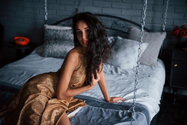 Piękne Czarne Włosy. Dziewczyna W Złotej Sukni Siedzi Przy Białym łóżku Na łańcuchach W Luksusowych Apartamentach Premium Zdjęcia