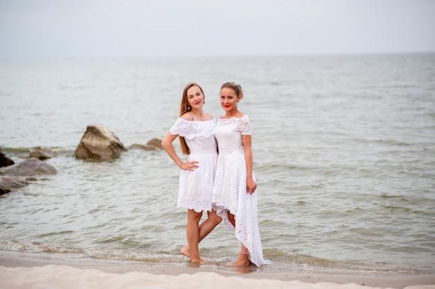 Piękne Dziewczyny W Białych Sukienkach Sfotografowane Na Morzu Premium Zdjęcia