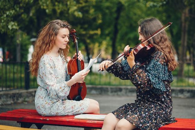 Piękne i romantyczne dziewczyny w parku ze skrzypcami Darmowe Zdjęcia
