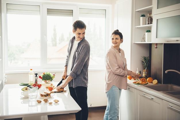 Piękne Kaukaski Coupe Uśmiechając Się Do Siebie, Przygotowując Razem Jedzenie W Kuchni Premium Zdjęcia