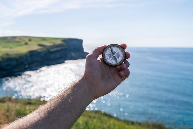 Piękne Klify I Krajobraz Otwartego Morza Ze Starym Kompasem Na Dłoni Podróżnika. Premium Zdjęcia