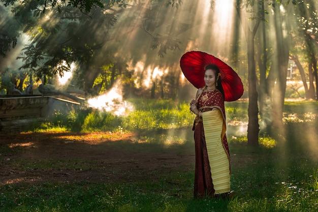 Piękne kobiety tajlandzkiej dziewczyny mienia ręki jaśminowa girlanda w tradycyjnym tajlandzkim kostiumu z świątynną ayutthaya jest tekstury złotem, tożsamości kultura tajlandia. Premium Zdjęcia