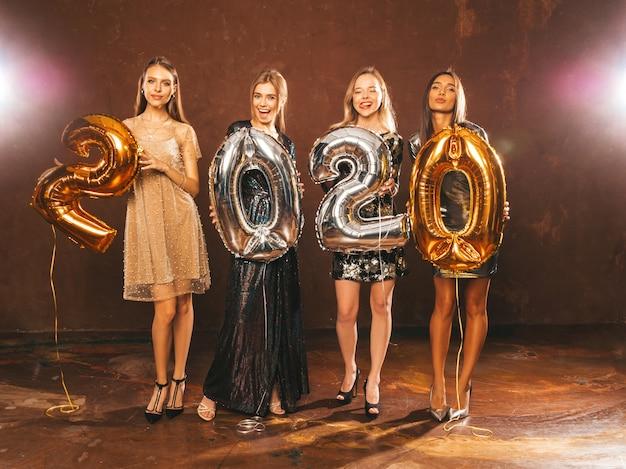 Piękne Kobiety Z Okazji Nowego Roku. Szczęśliwe, Przepiękne Dziewczyny W Stylowych Seksownych Sukienkach Na Imprezach Ze Złotymi I Srebrnymi Balonami 2020, Bawiące Się Na Imprezie Sylwestrowej. święto Bożego Narodzenia. Wspaniałe Modele Darmowe Zdjęcia