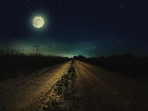 Piękne Magiczne Nocne Niebo Z Księżycem I Gwiazdami Oraz Droga Oddalająca Się W Oddali Z Zieloną Trawą Premium Zdjęcia