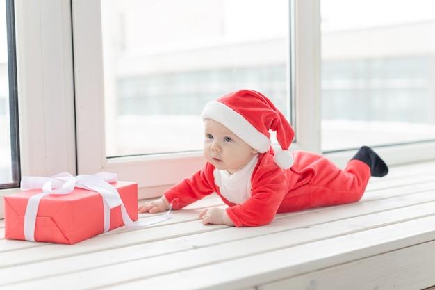Piękne Małe Dziecko Obchodzi Boże Narodzenie. święta Nowego Roku. Dziecko W świątecznym Stroju Iw Premium Zdjęcia