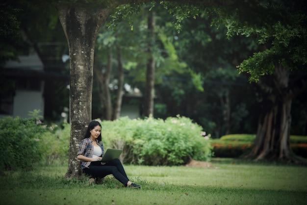 Piękne młode kobiety czyta książkę w parku plenerowym Darmowe Zdjęcia