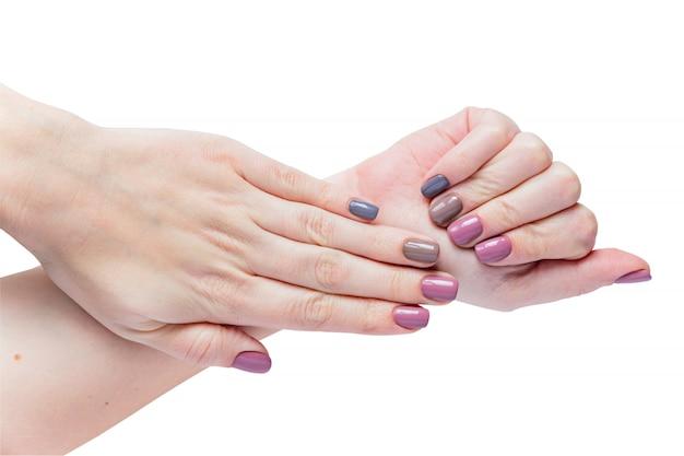 Piękne Młodych Kobiet Ręki Odizolowywać Na Białym Tle. Stylowy Modny Kobiecy Manicure Z Szarym, Różowym I Brązowym Lakierem Do Paznokci. Premium Zdjęcia