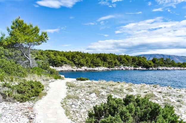 Piękne Morze Adriatyckie W Chorwacji. Błękitna Laguna, Zielone Sosny, Kamieniste Wybrzeże. ścieżka Wzdłuż Morza, Fajnie Premium Zdjęcia