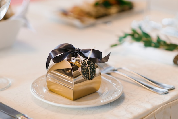 Piękne pudełko ze złotej folii z brązową satynową kokardą, weselny bonbonniere, na białym talerzu do serwowania na stole bankietowym Premium Zdjęcia