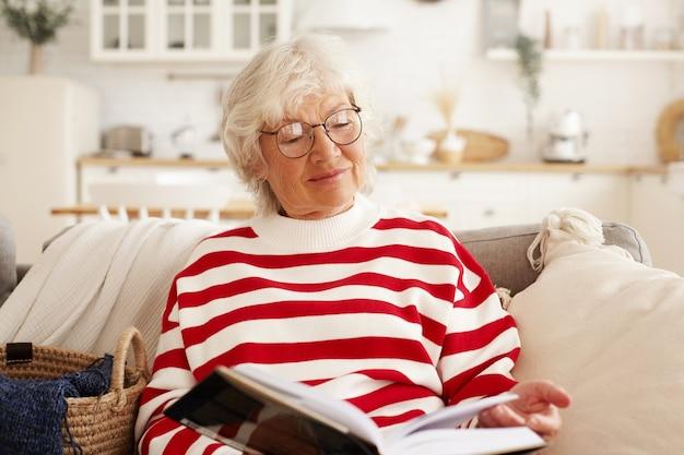 Piękne Siwowłosy Starszy Europejczyk W Stylowych Okularach Okrągłych, Ciesząc Się Czytaniem Powieści, Siedząc Na Kanapie Z Książką. Urocza Babcia Odpoczywa W Domu, Przeglądając Ekscytujący Podręcznik Darmowe Zdjęcia