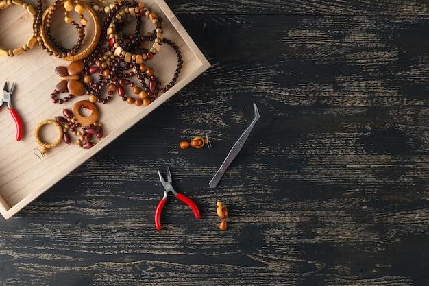 Piękne Tło Dla Warsztatów. Narzędzia Do Tworzenia Biżuterii, Kolorowe Kamienne Koraliki I Znaleziska Metalowe. Premium Zdjęcia