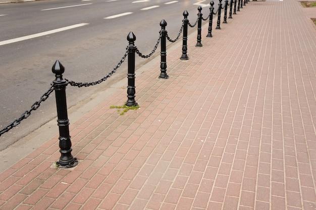 Piękne Ujęcie Ceglanego Chodnika Z Czarnymi Nowoczesnymi Metalowymi Słupami Bezpieczeństwa Darmowe Zdjęcia
