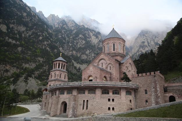 Piękne Ujęcie Chrześcijańskiego Kościoła Z Drzewami I Górami W Gruzji Darmowe Zdjęcia