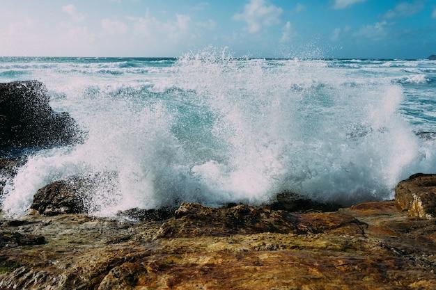 Piękne Ujęcie Fal Morskich Uderzających W Duże Skały W Pobliżu Brzegu Darmowe Zdjęcia