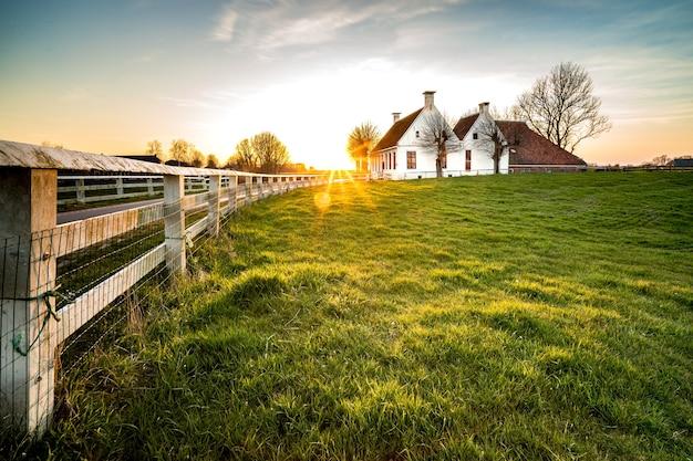 Piękne Ujęcie Ogrodzenia Prowadzącego Do Domu W Zielonej Trawie Darmowe Zdjęcia