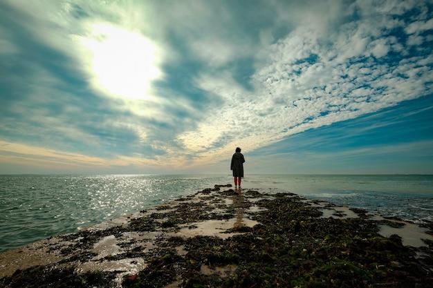 Piękne Ujęcie Osoby Spacerującej Po Lądzie W Oceanie Pod Pochmurnym Niebem Darmowe Zdjęcia