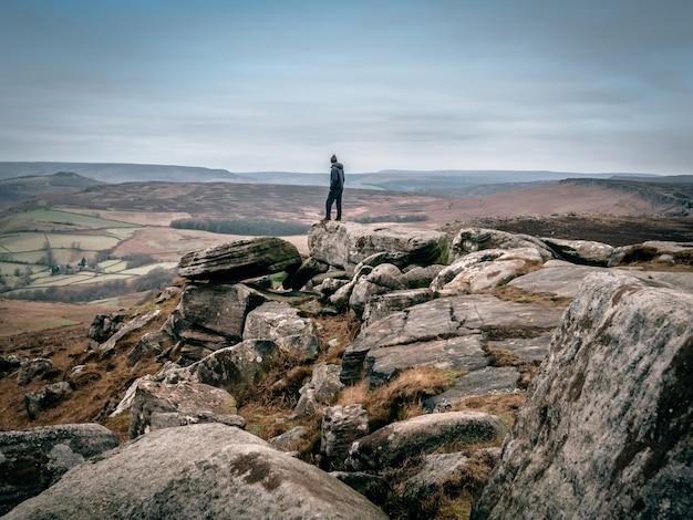 Piękne Ujęcie Osoby Stojącej Na Skałach I Spoglądającej Na Dolinę W Oddali Darmowe Zdjęcia
