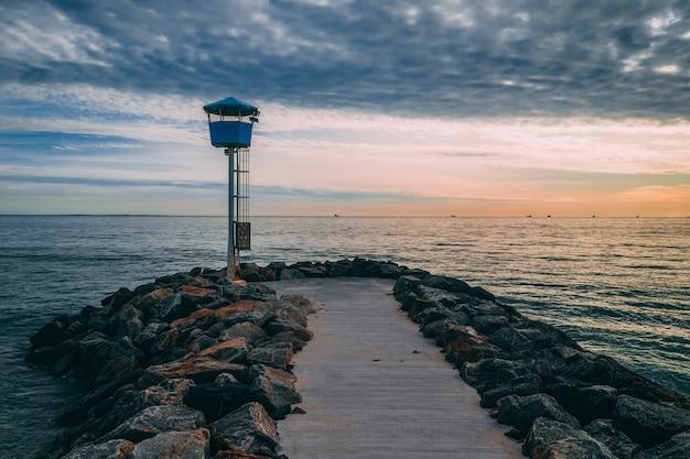 Piękne Ujęcie Przystani Otoczonej Kamieniami Prowadzącymi Do Morza O Zachodzie Słońca Darmowe Zdjęcia