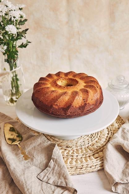 Piękne Ujęcie Pysznego Tortu Na Białym Talerzu I Białego Kwiatu W Pobliżu Darmowe Zdjęcia