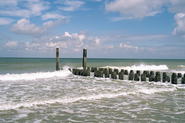 Piękne Ujęcie Wysokich I Krótkich Kamieni Z Mchem Na Szczycie Prowadzących Do Falującego Morza Darmowe Zdjęcia