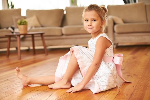 Piękne Urocze Dziewczynki Ubrane W świąteczną Sukienkę Z Pełną Spódnicą, Siedząc Boso Na Podłodze W Kuchni Darmowe Zdjęcia