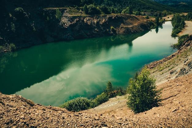 Piękne Zielone Jezioro O Wydłużonym Kształcie Ze Skalistym Wybrzeżem Z Kruszonego Kamienia Otoczonego Roślinnością. Zalany Głęboki Kamieniołom Do Wydobywania Minerałów. Premium Zdjęcia