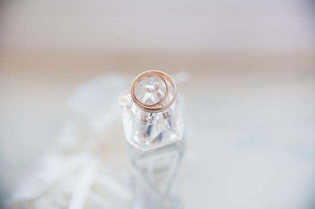 Piękne Złote Pierścienie Leżą Na Słoiku Perfum Premium Zdjęcia