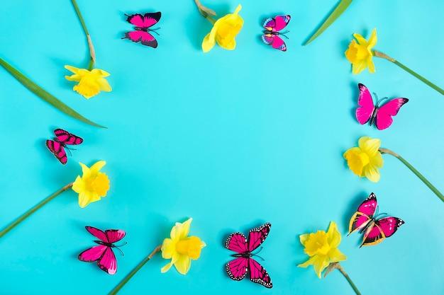 Piękne żółte Kwiaty żonkile, Motyl Na Niebieskim Tle Premium Zdjęcia