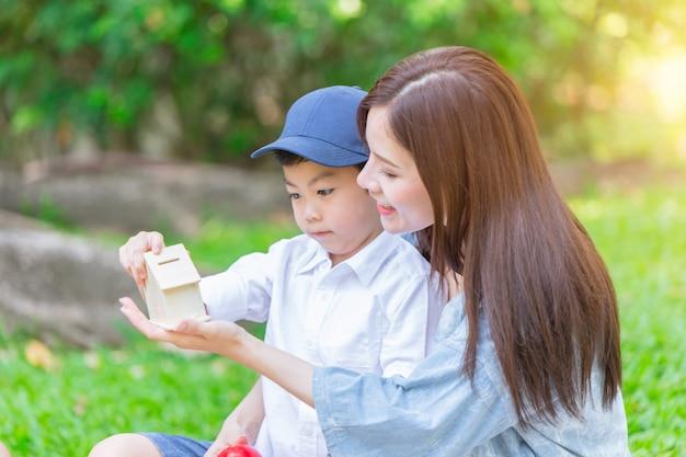 Pięknego Azjata Macierzysty Bawić Się Z Jej Uroczym Synem W Zielonym Parku Premium Zdjęcia