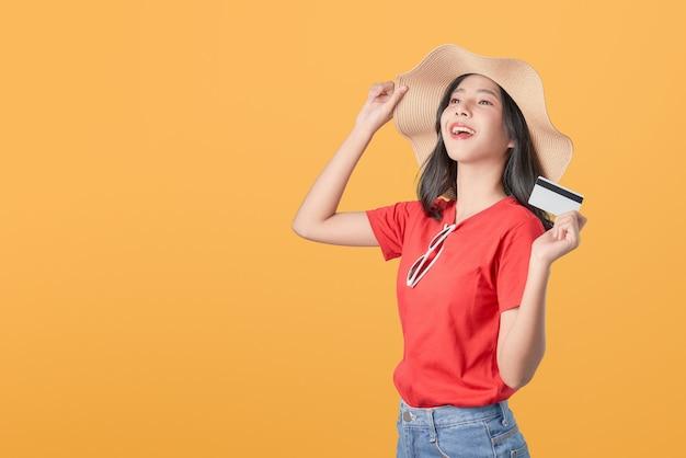 Pięknej azjatyckiej kobiety dobra skóra jest ubranym kapeluszową trzyma kredytowej karty zapłatę na pomarańczowym tle. Premium Zdjęcia