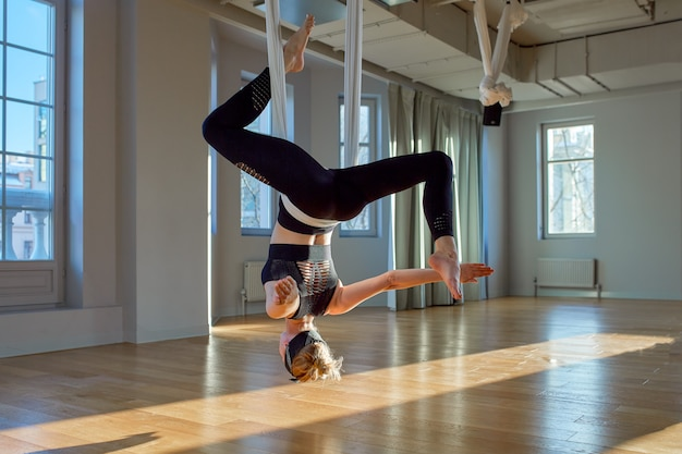 Pięknej dziewczyny powietrzny trener jogi pokazuje medutiruet na wiszących liniach do góry nogami w pokoju do jogi Premium Zdjęcia