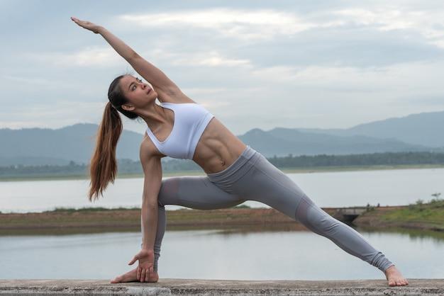 Pięknej kobiety ćwiczy joga jeziorem z górą. Premium Zdjęcia